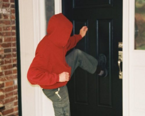 Burglar kicking in door