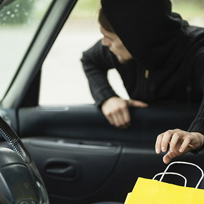 Man stealing shopping bag from car - holiday security tips
