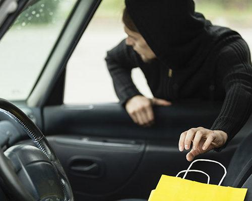 Man stealing shopping bag from car