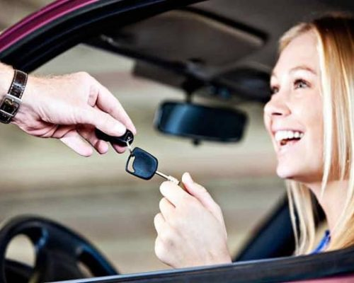 Mobile Locksmith handing replacement car key to smiling customer