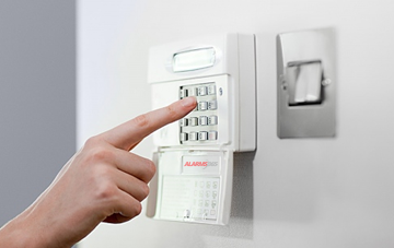 Person operating home security system keypad