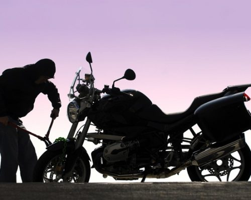 Prevent Motorcycle Theft | Silhouette photo of thief cutting chain during motorcycle theft | Lock N More
